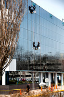Window cleaners rappel down building