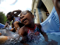 Kids frolic under the spray of a hose in a pool on the sidewalk in Trenton